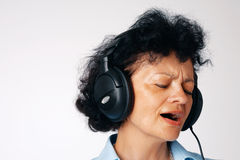 What a Song. Close-up portrait of a singing elder woman with headphones Stock Image