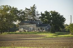 Abandoned House in the Country. What stories could this house tell? Why did someone abandon it? Alone it sits way off the road in the middle of a field with the Royalty Free Stock Photo