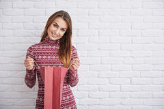 What a surprise. Portrait of happy woman in warm sweater holding present bag Stock Photos