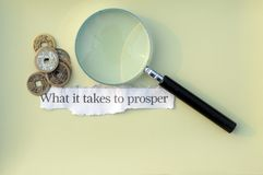 What it takes to prosper. Text words what it takes to prosper with magnifying glass stock photography