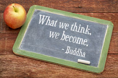 What we think we become. Buddha quote on a slate blackboard against red barn wood stock photo