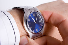 What is the time?. A Caucasian man checking the time on a silver watch with a blue face Stock Images