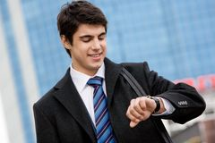 What time is it?. Photo of busy young man watching the time and smiling Stock Image