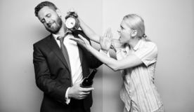 What is the time. Man suffering from alcoholism. Businessman with alcohol bottle and woman with alarm clock. Angry wife. What is the time. Man suffering from royalty free stock photography