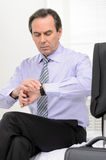What time is it? Mature businessman looking at his watch while s Stock Images