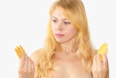What to choose. Young beautiful blonde  girl chooses that better 1 waffles or a little Stock Images
