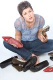 What to choose!. Young woman sitting on the floor tries to choose pair of shoes Royalty Free Stock Image