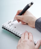 What to do. Woman's hand with a pen on a notebook Royalty Free Stock Images