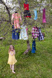 What to put on?. Little girl standing before the tree with dresses hanging on branches Stock Photo