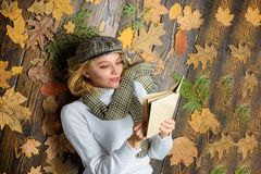 What to read in autumn book list. She likes detective genre. Girl blonde lay wooden background with leaves. Woman lady. In checkered hat and scarf read book stock images