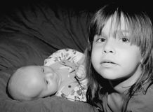 What about Us?. A small girl in a gesture of protection of her baby brother stock images