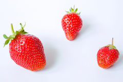 What vitamins include strawberries. Three fresh strawberries in three different size on a white background,photography Royalty Free Stock Photography