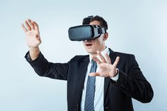 Businessman gesturing while wearing visual reality goggles. What is that. Waist up shot of an emotional entrepreneur keeping his mouth wide opened while getting Royalty Free Stock Photo