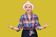 What? who? how? why? Portrait of confused sad stylish mature woman in casual style with hat and eyeglasses standing with raised. Arms, angry and asking. indoor stock image