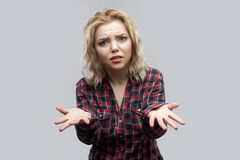 What? why? how? Portrait of confused beautiful blonde young woman in casual red checkered shirt standing and looking at camera. With raised arms. indoor studio stock photography