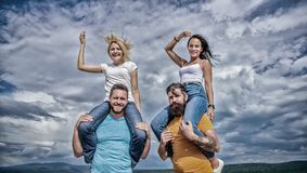 What we would call fun. Happy men piggybacking their girlfriends. Playful couples in love smiling on cloudy sky. Loving royalty free stock photo