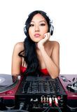 What would you like to hear?. A young female Asian DJ listening to music in front of her gear Stock Photos