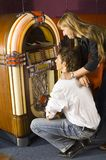 What would you like to play?. Couple of teenagers in front of jukebox. Smiling and looking at jukebox, choosing song Stock Photography