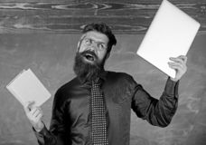 What would you prefer. Teacher bearded hipster holds book and laptop. Teacher choosing modern teaching approach. Digital. Against paper. Choose right teaching stock image