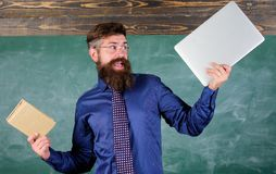 What would you prefer. Teacher bearded hipster holds book and laptop. Teacher choosing modern teaching approach. Paper. Book against laptop. Digital against royalty free stock images