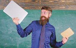 What would you prefer. Teacher bearded hipster holds book and laptop. Teacher choosing modern teaching approach. Paper. Book against laptop. Digital against royalty free stock photo