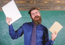 What would you prefer. Teacher bearded hipster holds book and laptop. Teacher choosing modern teaching approach. Digital. Against paper. Choose right teaching royalty free stock photo