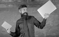 What would you prefer. Teacher bearded hipster holds book and laptop. Teacher choosing modern teaching approach. Paper. Book against laptop. Digital against stock photography