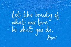 What you do Rumi. Let the beauty of what you love be what you do - ancient Persian poet and philosopher Rumi quote handwritten on blue wall Royalty Free Stock Images