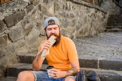 What are you eating today. Caucasian guy enjoy eating out. Bearded man eating unhealthy hotdog sandwich. Hipster eating royalty free stock photography
