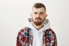 What are you looking at. Portrait of handsome stylish european student with flesh tunnels in ears, making serious and. Cool face while standing in trendy Stock Image