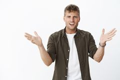 What you mean break up. Shocked and confused intense young boyfriend with blue eyes and fair hair raising hands sideways. In dismay and clueless pose open mouth royalty free stock photos