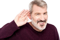 What you said, can't hear you !. Mature man cupping hand behind ear Stock Photos