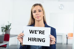 What are you waiting for we`re hiring. Business woman in a workplace holding a hiring sign as an invitation Royalty Free Stock Photo