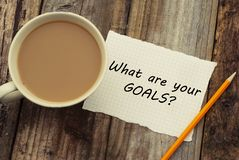 What Are Your Goals question as memo on white blank paper with cup of coffee. Rustci wooden background. stock image