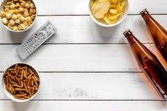 whatching用啤酒、面包屑、芯片和玉米花白色木背景顶视图大模型的戏院和电视 免版税库存照片