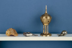 Whatnot and sundries on white shelf. On blue wallpaper background Royalty Free Stock Images