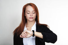 Whats the time. Woman in a suit looking at her watch Royalty Free Stock Images