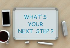 Whats Your Next Step, message on whiteboard, smart phone and coffee on table royalty free stock image