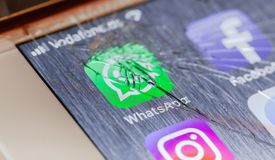 WhatsApp App on broken iPhone screen. BERLIN, GERMANY - OCTOBER 15, 2018: WhatsApp app on a broken screen of an iPhone 7 Plus with personalized background stock photo