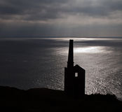 Wheal Prosper at Rinsey Head in Cornwall. Dramatic afternoon light bathes the preserved tin mine engine house of Wheal Prosper on Rinsey Cliff on the south west Royalty Free Stock Images