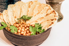 Arab flatbreads. Healthy crumpets with spicy chickpea and green parsley given on the medieval clay pots. Arab  pizza Royalty Free Stock Photos