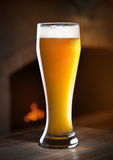 Wheat beer. Fireplace in the background Royalty Free Stock Image
