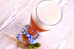 Wheat beer in glass with blue ribbon on white wood background Stock Images