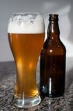 Wheat beer glass and brown bottle Stock Photos