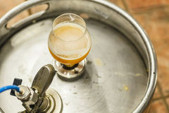 Wheat beer on a keg. Glass of opaque wheat beer standing on a stainless steel keg at a brewery Royalty Free Stock Image