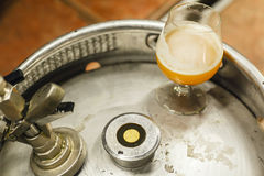 Wheat beer on a keg. Glass of opaque wheat beer standing on a stainless steel keg at a brewery Royalty Free Stock Photos