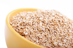 Wheat bran. Bowl of wheat bran on white background. It is common ingredient of healthy meal Royalty Free Stock Image