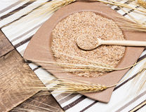 Wheat bran in bamboo plate with wheat ears. Bamboo plate and wooden spoon filled with wheat bran surrounded by wheat ears on striped cloth napkin and wooden Stock Image