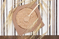 Wheat bran in bamboo plate and wooden spoon with wheat ears Royalty Free Stock Photo