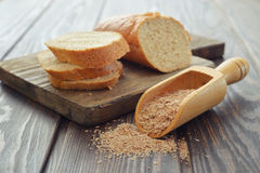 Wheat bran in bowl. Wheat bran in scoop with sliced bread on wooden background Royalty Free Stock Image